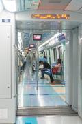 Passengers riding a high-tech, monorail commuter train through downtown Dubai - stock photo