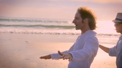 Slow mo hand held shot of two male friends surfing an imaginary wave - stock footage