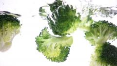 Broccoli florets falling into water - stock footage