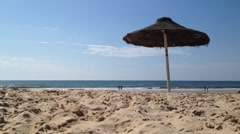 Stock Video Footage of View of Praia Verde in Castro Marim, Algarve, Portugal. Straw umbrella on a b