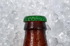 Single beer bottle cap cooling down on pile of ice Stock Photos