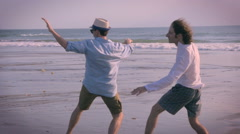 Handheld Slow motion of two men pretending to surf in the wind on the beach Stock Footage