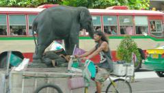 Homeless person sleeping beneath an elephant statue. Bangkok, Thailand Stock Footage