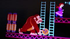 Medium Macro of 'Donkey Kong' gorilla character rolling barrels while damsel Stock Footage