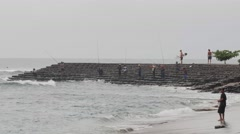 Fishermen and surfers on rock wall Stock Footage