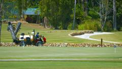 Maintenance utility vehicle drives past a putting green at golf course Stock Footage