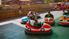 Local residents enjoying a bumper car ride at an amusement park Stock Footage