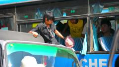 Young Burmese man exits a parked bus via a window. Myanmar Stock Footage
