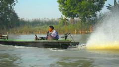 Burmese boatman piloting his small, motorized passenger canoe Stock Footage