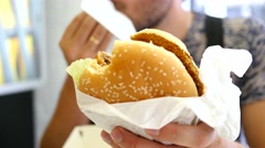 Man eating tasty burger in fast food restaurant Stock Footage