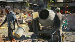 Manual laborers pouring dry cement into a diesel mixer. Myanmar Stock Footage