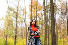 Portrait of young beautiful serious  woman standing at autumn park - stock photo