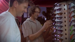 Two male tourists shopping for sunglasses together at a tourist stand Stock Footage