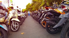 Motorbikes parked in long rows in a downtown area of Kuta, Bali Stock Footage