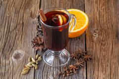 Mulled wine and spices on weathered wooden table - stock photo