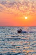 Man riding jet ski on colorful sunset Stock Photos