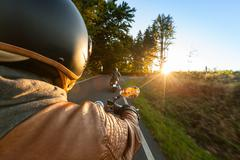 Biker riding motorcycle  in sunny morning Stock Photos
