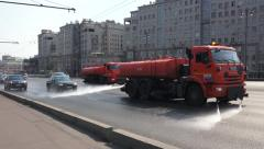 Water trucks 'cleaning' a road during the summer in Moscow, Russia. Stock Footage