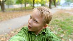 Funny kid blowing kiss at camera while making selfie. Funny face of boy Stock Footage