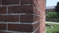 The camera moves along a brick wall of a house or home. - stock footage