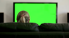 Back view of woman sitting on black leather couch watching green screen TV - stock footage