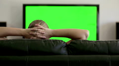 Arms behind her head, a woman watches Green screen on the television. - stock footage