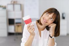 Thoughtful Office Woman Holding Coffee Cup - stock photo