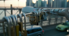 Lovers' locks swing in the wind over traffic on Brooklyn Bridge New York City Stock Footage