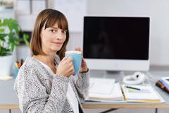 Office woman holding a cup of coffee - stock photo