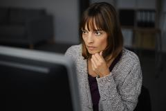 Businesswoman Working on her Computer Seriously - stock photo