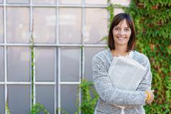 Businesswoman Hugging Newspaper Outside a Building Stock Photos