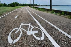 Asphalt road with bicycle sign and markings near a water - stock photo