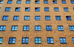 Brick wall of tall building with many windows Stock Photos