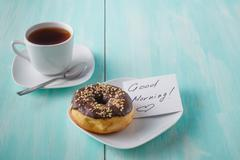 Donuts on saucer with note Good morning Stock Photos