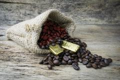 Coffee beans and Gold Bullion in sackcloth bag on wooden background - stock photo