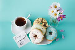 """Donuts with flowers and note """"Good Morning"""" - stock photo"""