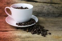 Cup full of coffee beans on wood - stock photo