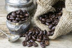 Silver cup and Coffee beans in sackcloth bag on wooden background - stock photo