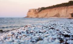 Pebble limestone beach during sunset Stock Photos