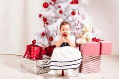 New year concept. Child baby toddler kid sitting under decorated christmas tree Kuvituskuvat