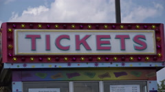 Booth selling tickets for rides at carnival on sunny day 4k Stock Footage