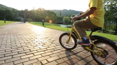 Asian boy riding bicycle at park in sunset - stock footage