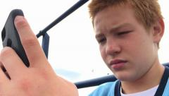 Young boy using cell phone texting with focus on hands 4k - stock footage