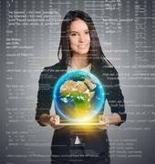 Smiling woman holding Earth globe over tablet on computer code background - stock photo