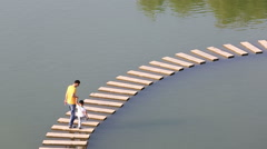Shanghai,China-October 4,2015: Father and son walking on the stone bridge ove Stock Footage