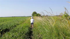 Boy walking the path in the grass Stock Footage