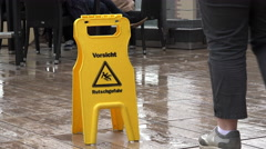 Warning wet floor sign in Germany with people walking by 4k Stock Footage