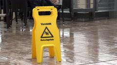 Wet floor sign on rain covered patio 4k Stock Footage