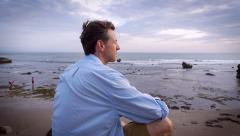 Slow motion handheld portrait of a man sitting and overlooking the ocean - stock footage