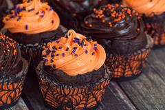 Orange and dark chocolate Halloween cupcakes Stock Photos